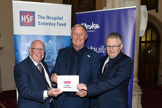 John Greenwood, HSF Chairman, and Paul Jackson, HSF Chief Executive award a cheque to Chris Tarrant on behalf of the Stroke Association